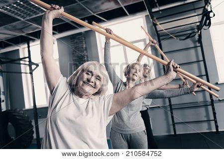 Sport brings joy. Three pleasant lively senior women standing one behind another in a gym and doing stretching exercises with wooden sticks while smiling happily