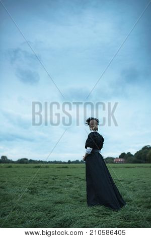 Historical Woman In Black Dress In Countryside With Cloudy Sky