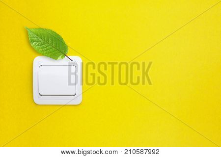 Light switch with green leaf. Saving energy concept.