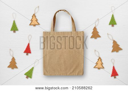 Canvas bag and handmade Christmas decorations on white wooden background. Christmas sale concept.
