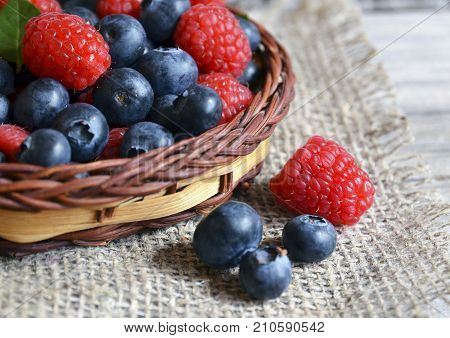 Fresh organic blueberries and raspberries.Freshly picked raspberries and blueberries in a basket on a burlap cloth background.Blueberry and raspberry.Healthy eating,diet concept.Selective focus.