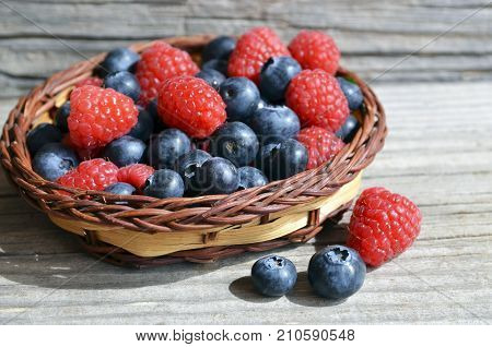 Fresh organic blueberries and raspberries. Freshly picked raspberries and blueberries in a basket on old wooden background.Blueberry and raspberry.Healthy eating,diet concept.Selective focus.