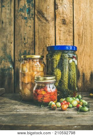 Autumn seasonal pickled vegetables and fruit in glass jars, rustic wooden barn background. Fall preserved vegetarian food concept, copy space