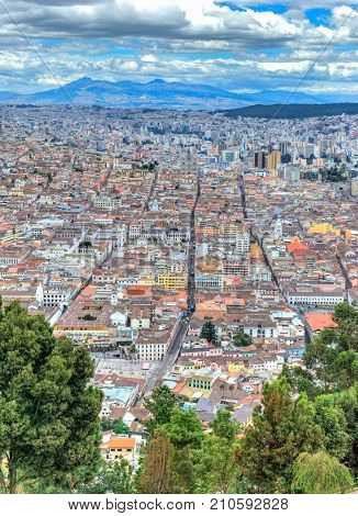 High view of Quito, from the Panecillo hill, on a cloudy and overcast afternoon. Quito, Ecuador.