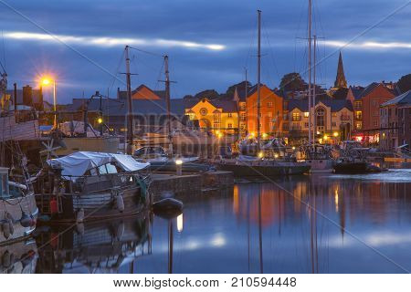 Pier in the city of Exeter. Night time. Small vessels and boats are moored. Street lighting is on. Devon. England