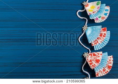 Garland with Christmas trees made of paper forms for muffins. Christmas DIY concept. Festive background with space for text