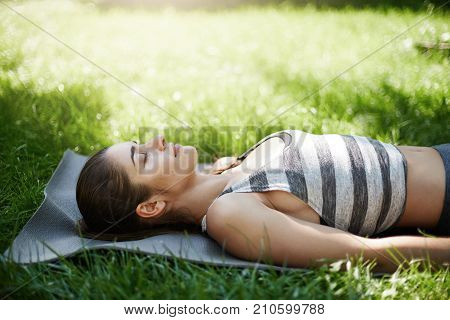 Portrait of young female laying on yoga mat in park meditating dreaming about her future. Sunny summer day outside is a great time to go outoors.
