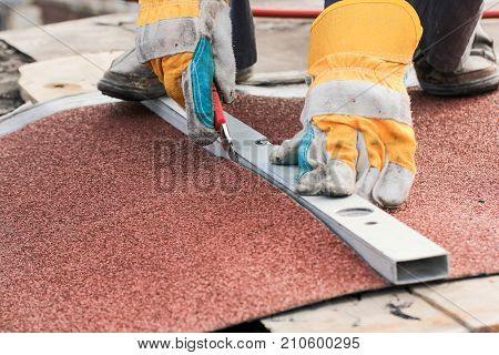 Trimming the material into size. Roofing works with soft-fill materials.