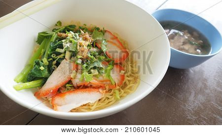Egg noodle Cantonese recipes with BBQ pork and bone soup in set on wood desk brawn color paint Testy and popular of fast food has copy space.