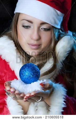 Christmas Girl In A Red Coat.winter Woman. Snow In Hands