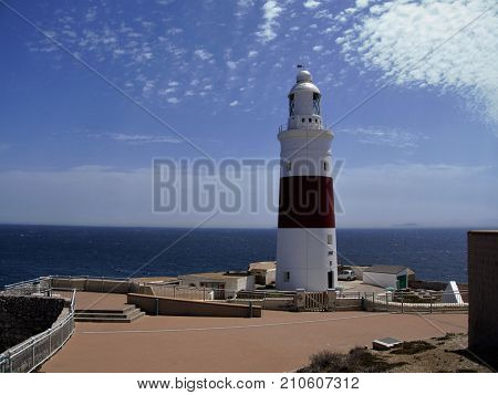 Lighthouse in Gibraltar on penninsula on sky and sea background