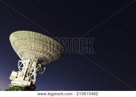 huge white satellite antenna radio telescope on the background of star at night