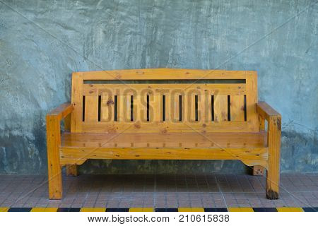 Yellow wooden bench stand beside the road with raw exposed cement wall.