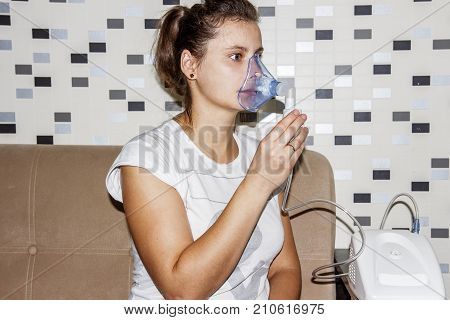woman uses an inhaler at home when she coughs. Treatment of respiratory diseases. Inhalation with bronchitis