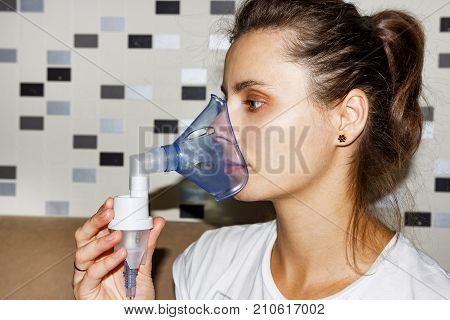 woman breathes into an inhaler mask closeup. Treatment of coughing with bronchitis. Inhalation of the house.