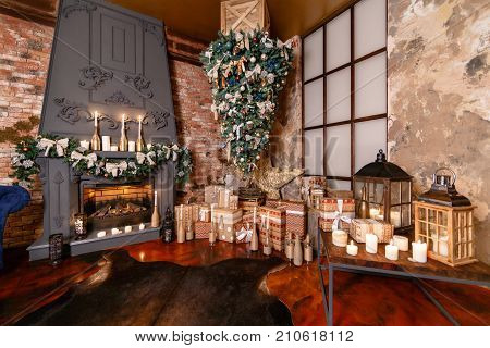 alternative tree upside down on the ceiling. Winter home decor. Christmas tree in loft interior against brick wall. Old vintage furniture.