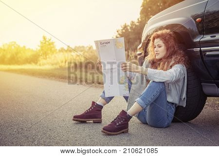 Travel. Beautiful Redhair Girl Sitting On The Road With Map