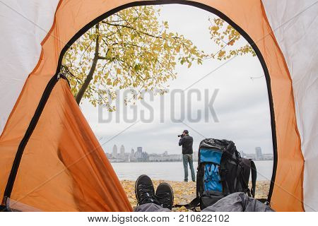 View from the tent with legs. Legs in a tent with a beautiful view outside. Silhouette of a man taking pictures on the river bank. Focus on shoes. A backpack next to the tent.