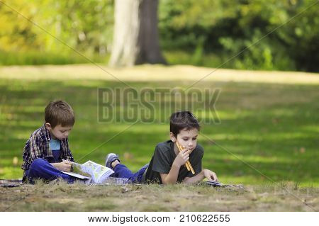 children lie on the grass and read books. boys eating breadsticks and reading outdoors. The concept of the home schooling