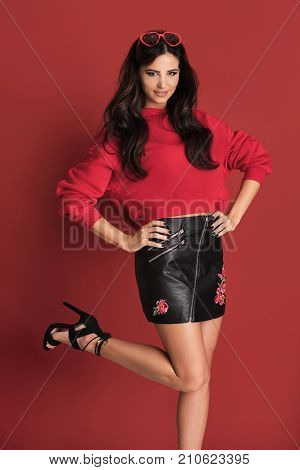 Fashionable Beautiful Woman Posing On Red Background.
