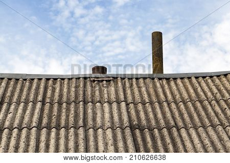old slate of gray color, lying on the roof to protect from rain. Photo close-up, countryside. on the top of the roof sticks out a metal chimney