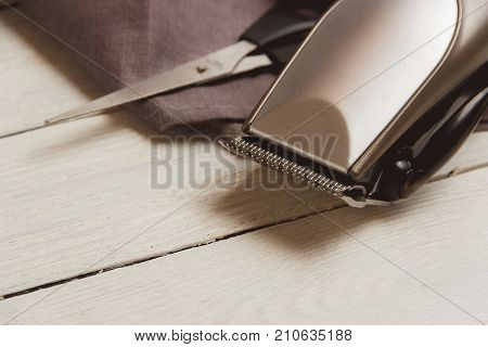 Stylish Professional Barber Clippers, Hair Clippers, Haircut accessories on wood background with copy space