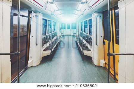 View of bright empty interior of modern subway train car while it is waiting on station with yellow doors opened; contemporary underground railway carriage indoors with no one inside empty seats
