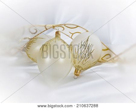 gold glitter and white Christmas ornaments on white satin with fancy ribbon