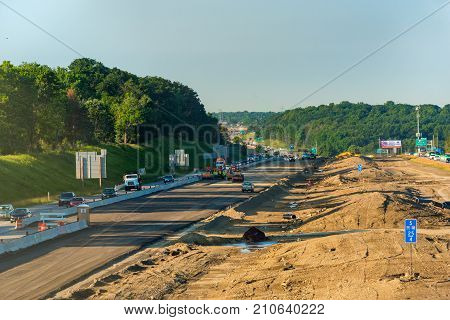 BEDFORD HEIGHTS OH - JUNE 28 2017: Crews begin to lay asphalt on new lanes in a major construction project on Interstate 271 southeast of Cleveland Ohio.