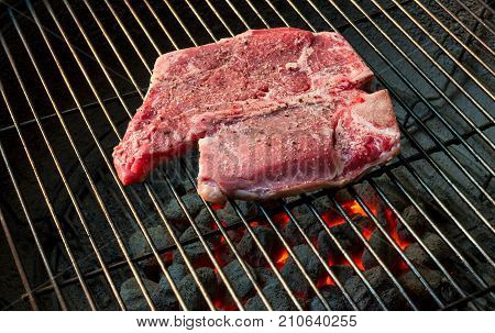 A T-bone steak on a grill raw side up with seasoning