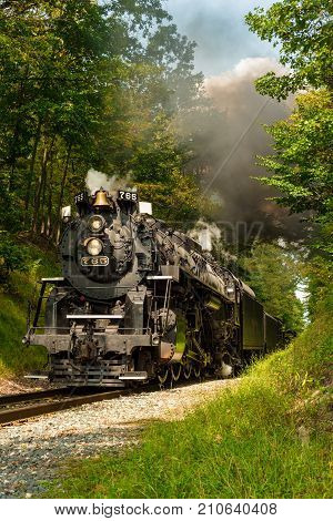 PENINSULA OH - SEPTEMBER 17 2917: The NKP-765 one of the largest steam locomotives still in existence emerges from a narrow pass through woods south of Cleveland.