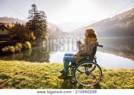Senior woman in a wheelchair in an autumn nature. A woman praying by the lake in the early morning.