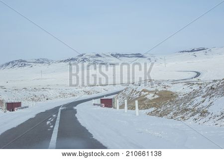 Landscape of curve asphalt road surrounding by snow with mountain range and white sky background in winter season near Lake Khovsgol at Mongolia, View of clear empty way curve left and right through lowland covered in snowy its make feel cool and isolated