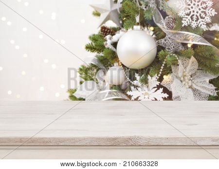 Wooden table in front of blurred decorated Christmas tree background