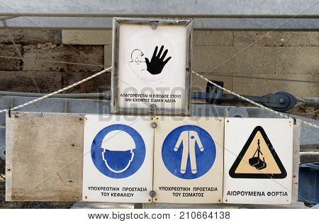 """Construction safety signs with inscriptions in the Greek language (""""Forbidden to enter without special permission """"Mandatory head protection"""" """"Mandatory body protection"""" """"Suspended freights""""). poster"""
