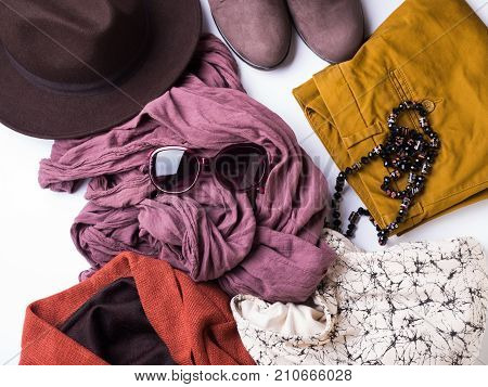 Flat lay with lady's clothes, hat, sun glasses, necklace. Autumn colours accessories on white background