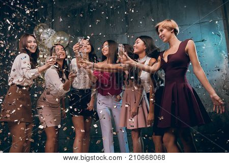 Celebrating with fun. Group of cheerful young girls carrying champagne flutes and dancing in gold confetti. The best party in 2018 year. Happy New year!