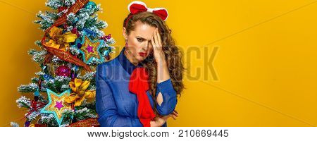 Stressed Woman Near Christmas Tree Isolated On Yellow Background