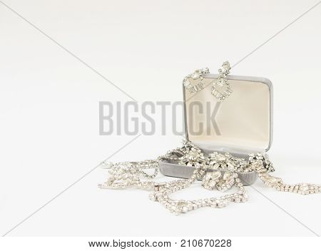 Woman's Jewelry. Vintage jewelry background. Beautiful rhinestone brooches and necklace in a jewelry box on white background