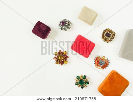 Woman's Jewelry. Vintage jewelry background. Beautiful bright rhinestone brooches and jewelry boxes on white background. Flat lay, top view with copy space
