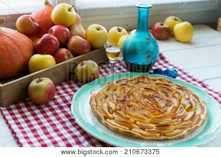 a beautiful apple pie with apples and bottle of Calvados