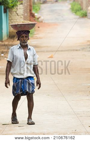 PONDICHERY PUDUCHERY INDIA - September 02 2017. Unidentified indian man have bricks in a plate on their head for the house construction. Concept of manual labor very hard.