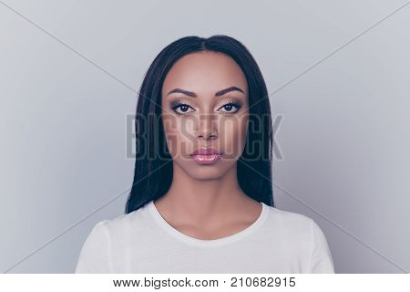 Close Up Portrait Of Young Brunette Afro Lady With Serious Grimace, On Pure Grey Backgrund And Looki