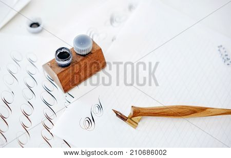 letter in caligraphic handwriting. pen for writing ink on a background of a table with paper and a stencil for learning the perfect handwriting.