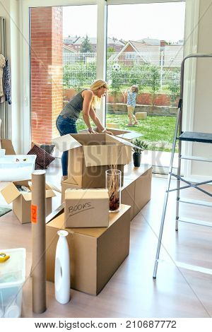 Woman unpacking moving boxes while her son and her husband play in the garden
