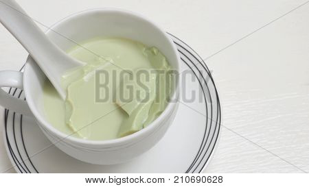 Drink background Tofu green tea ceramic white cup and plate kitchen ware set close up Isolate on wood white texture and copy space.