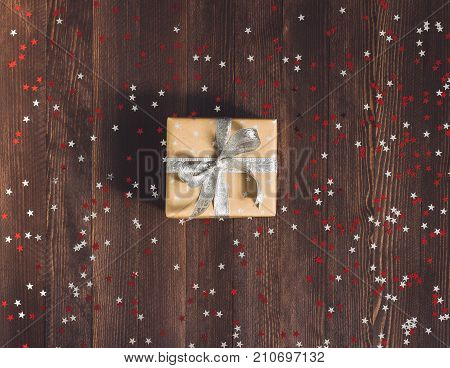 Christmas holiday gift box on decorated festive table with sparkle stars on wooden background. Packaging gift wrap. Winter time new year