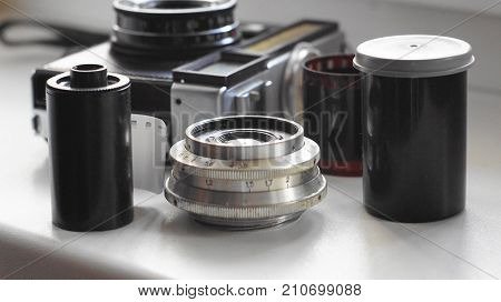 A still life of accessories from old film cameras: camera, lens, film cassette, piece of film, film container.