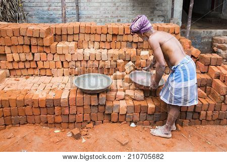 PONDICHERY PUDUCHERY INDIA - September 02 2017. An unidentified indian man puts bricks in a plate for the house construction. Concept of manual labor very hard.
