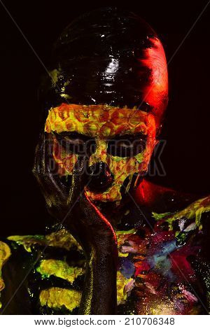 Halloween life and death concept. Woman skeleton with flower on chest. Day of dead celebration. Girl with skull face paint on black background. Body painting and art.